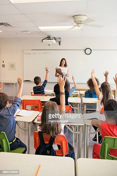 """elementary students with hand raised in class with teacher. - """"martine doucet"""" or martinedoucet stock pictures, royalty-free photos & images"""