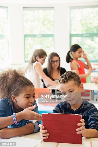 """estudiantes de primaria trabajando en equipo en tableta electrónica en el aula. - """"martine doucet"""" or martinedoucet fotografías e imágenes de stock"""