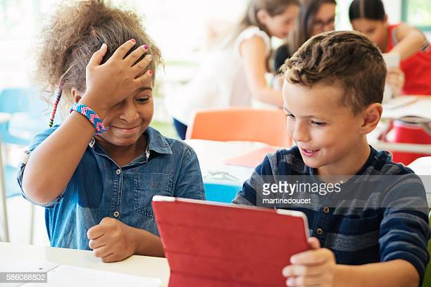 """elementary students working in team on electronic tablet in classroom. - """"martine doucet"""" or martinedoucet stock pictures, royalty-free photos & images"""