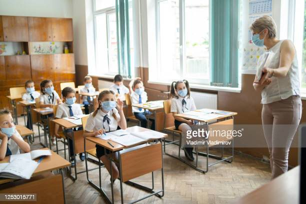covid-19. elementary teacher doing classes during coronavirus pandemic - reopening stock pictures, royalty-free photos & images