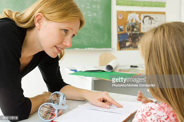 elementary teacher helping student with work - teacher bending over stock photos and pictures