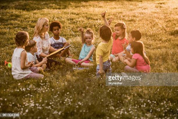 elementary teacher holding a class to group of kids at the park. - q and a stock pictures, royalty-free photos & images