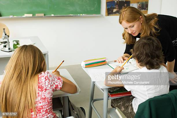 elementary teacher leaning over student's desk, helping him with assignment - teacher bending over stock photos and pictures