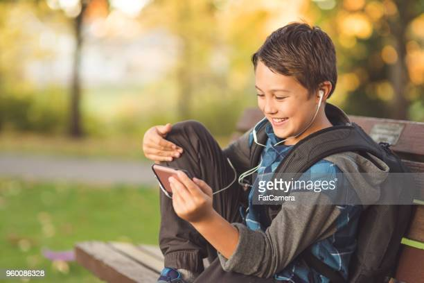 elementary-age boy sits on a park bench and watches a video on his phone - pre adolescent child stock pictures, royalty-free photos & images