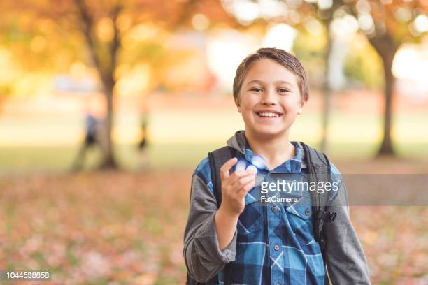 elementary-age boy walking to school and holding a fidget spinner - autism spectrum disorder stock photos and pictures