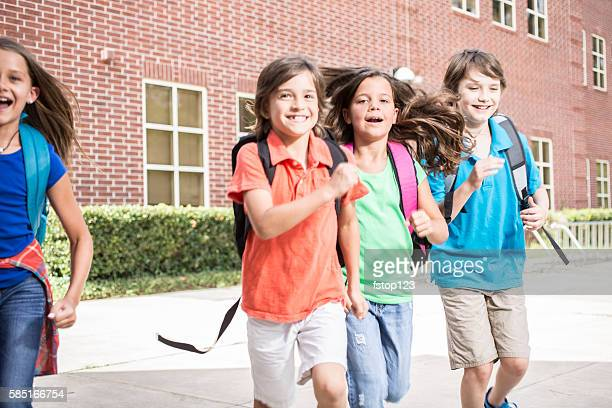 Elementary-age children, friends run on school campus.