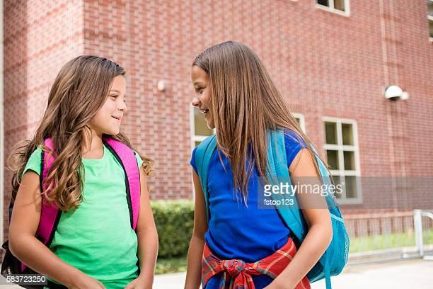 elementary-age children on school campus going back to school. - schulkind nur mädchen stock-fotos und bilder