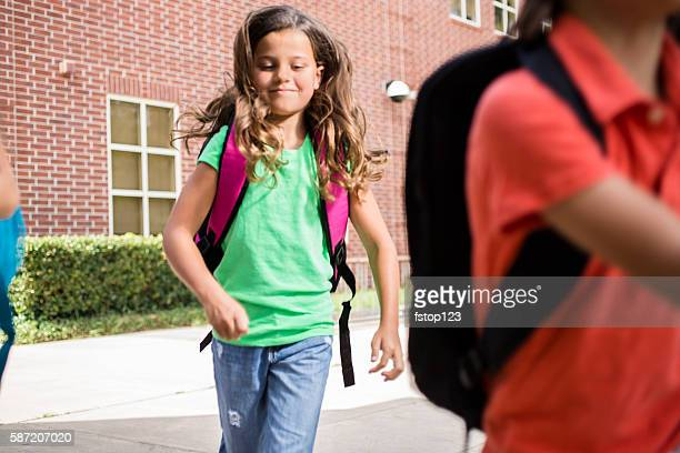 Elementary-age children run on school campus.