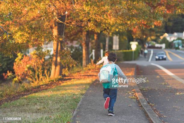 elementary-age classmates running to school with their backpacks - district stock pictures, royalty-free photos & images