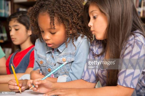 Elementary-age school girls collaborate on homework.