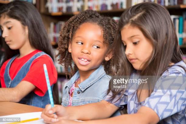 Elementary-age school girls collaborate on homework.