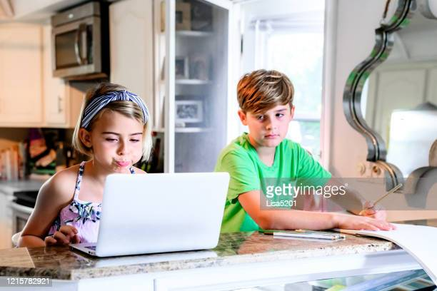 elementery age children siblings work on schoolwork from home using computer acting silly - lisa strain stock pictures, royalty-free photos & images