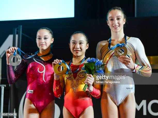 Elena Eremina of Russia Yilin Fan of People's Republic of China and Nina Derwael of Belgium pose with their medals after competing on the uneven bars...