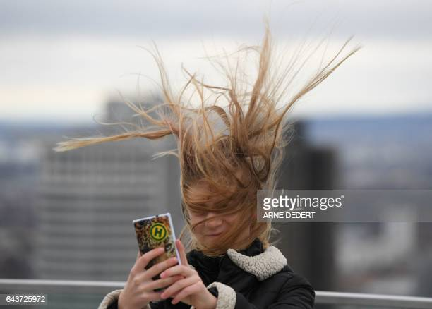 Elena from Dresden has her hair ruffled by the wind as she stands on a visitors' platform on the Maintower in Frankfurt am Main western Germany...
