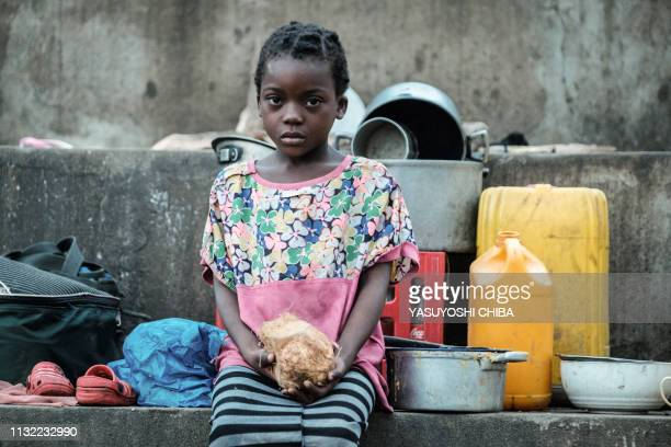 TOPSHOT Elena Joaquin holds a coconut as she stays in shelter with her family at the stands of Ring ground in Buzi Mozambique on March 23 2019 The...
