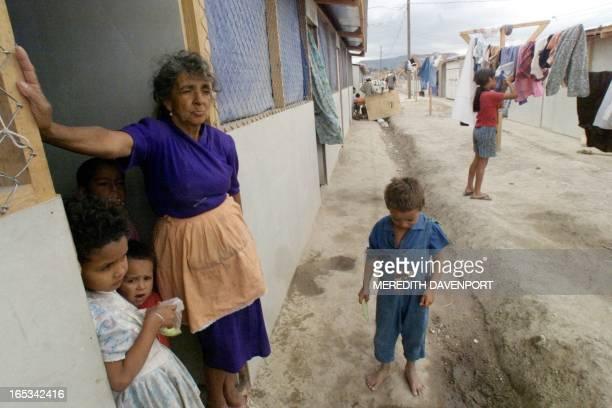 Elena Lagos and her grandchildren, survivors of Hurricane Mitch, stand the doorway of her temporary home 07 March El Trebol refuge in Tegucigalpa....