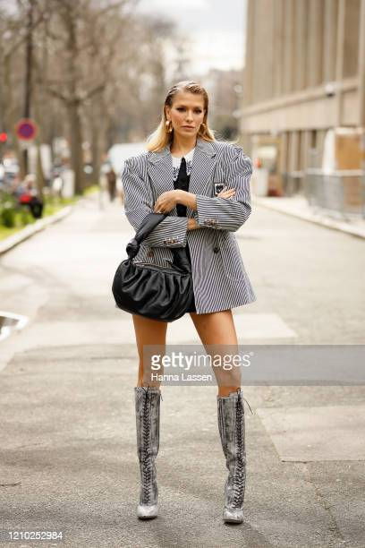 Elena Perminova is seen wearing a Miu Miu black and white jacket, lace up boots and black bag outside the Miu Miu show during Paris Fashion Week...