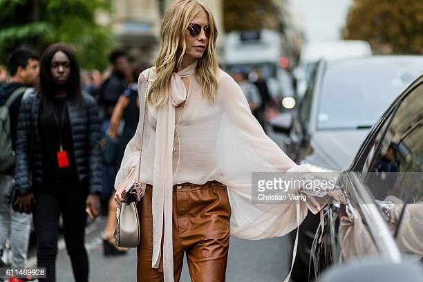 Elena Perminova wearing a white blouse and brown leather pants outside Chloe on September 29, 2016 in Paris, France.