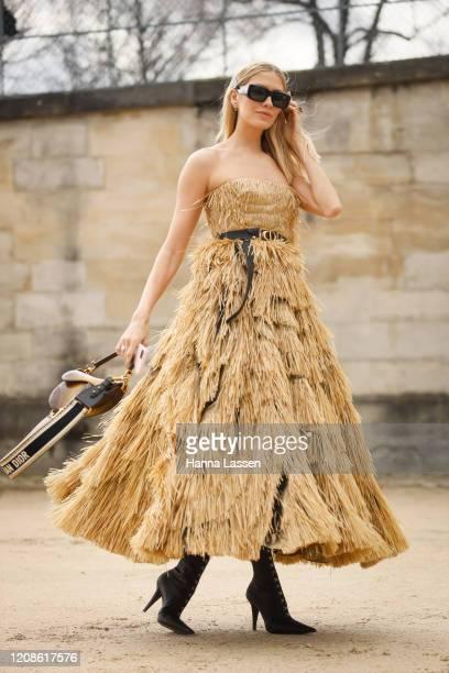 Elena Perminova wearing gold fringe Dior dress, Dior belt, Dior saddle bag and Dior sunglasses outside the Dior show as part of the Paris Fashion...
