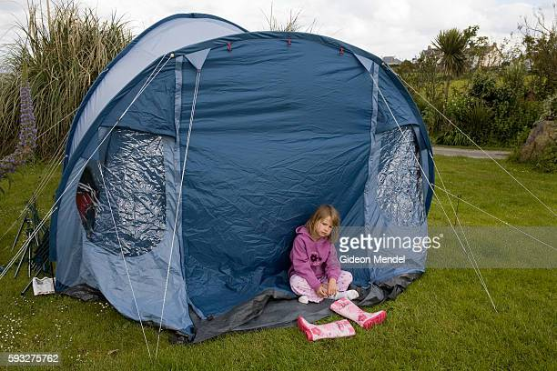 Elena Philipson sits outside her family tent on a rainy morning in Henry's Campsite on the Lizard Peninsula in Cornwall Henrys Campsite is a small...