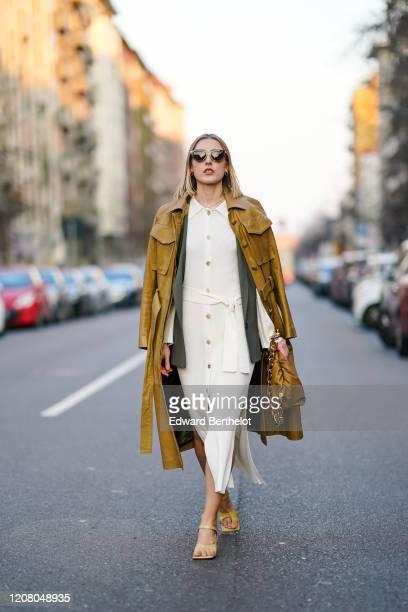 Elena Ricciardi wears sunglasses a brown leather long coat a white dress a green khaki jacket a brown bag with a golden chain strap outside Bottega...