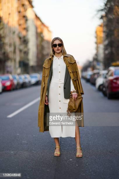 Elena Ricciardi wears sunglasses, a brown leather long coat, a white dress, a green khaki jacket, a brown bag with a golden chain strap, outside...