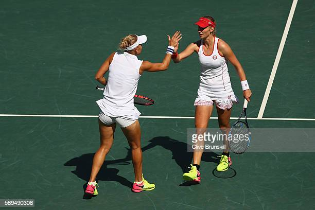 Elena Vesnina and Ekaterina Makarova of Russia celebrate a point during the women's doubles gold medal match against Martina Hingis and Timea...