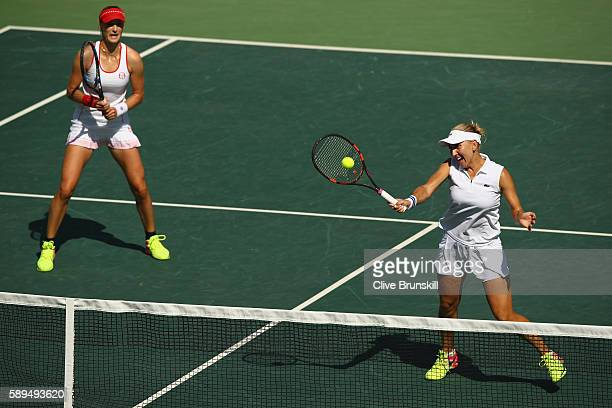 Elena Vesnina and Ekaterina Makarova of Russia in action during the women's doubles gold medal match against Martina Hingis and Timea Bacsinszky of...