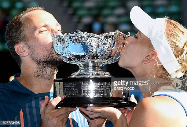 Elena Vesnina of Russia and partner Bruno Soares of Brazil kiss the winner's trophy at the awards ceremony following their victory over Coco...
