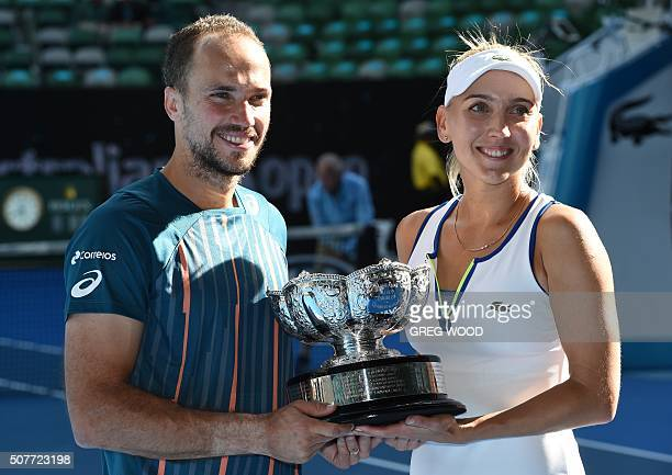 Elena Vesnina of Russia and partner Bruno Soares of Brazil pose with the winner's trophy at the awards ceremony following their victory over Coco...