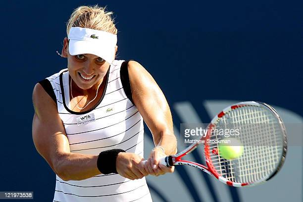 Elena Vesnina of Russia returns a shot to Anabel Medina Garrigues of Spain during the New Haven Open at Yale presented by First Niagara at the...