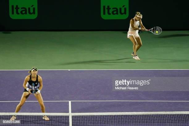Elena Vesnina returns a shot to Lyudmyla Kichenok of Ukraine and Alla Kudryavtseva of Russia while playing with Ekaterina Makarova of Russia during...