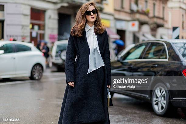 Eleonora Carisi is wearing a long black wool coat and a whire blouse seen outside Giorgio Armani during Milan Fashion Week Fall/Winter 2016/17 on...