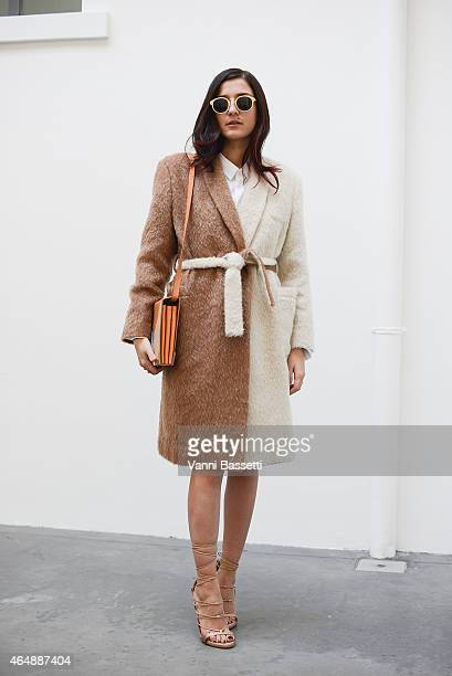 Eleonora Carisi poses wearing an Au Jour Le Jour coat and Benedetta Bruzziches bag on March 1 2015 in Milan Italy