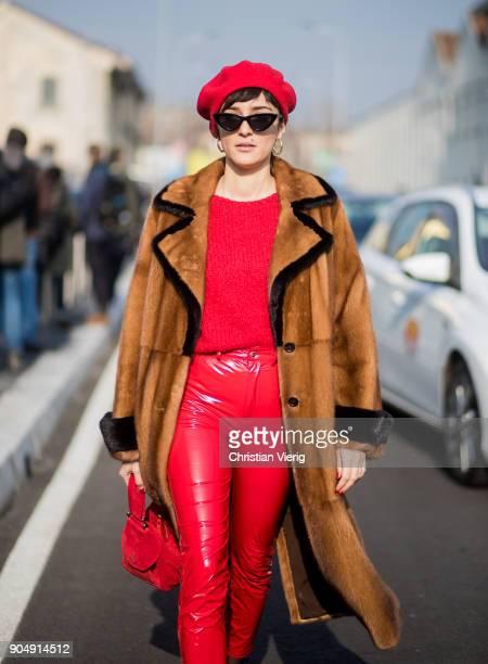 Eleonora Carisi wearing red vinyl pants red flat cap red bag brown fur coat is seen outside DSquared2 during Milan Men's Fashion Week Fall/Winter...