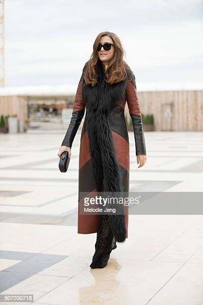 Eleonora Carisi wears a brown and black leather stripe coat with a black fur lining and lace sheer pattern pants at the Elie Saab Couture show at...