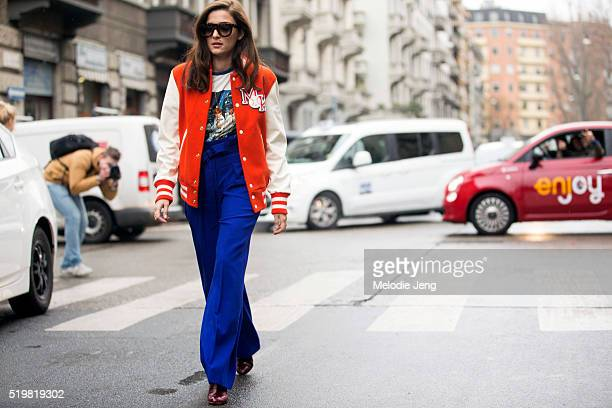 Eleonora Carisi wears an orange Reebok embroidered bomber varsity jacket a graphic print tshirt and blue Korsun highwaisted trousers at the Antonio...