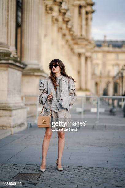 Eleonora Carisi wears sunglasses a gray pleated dress a bag shoes earrings outside Louis Vuitton during Paris Fashion Week Womenswear Fall/Winter...
