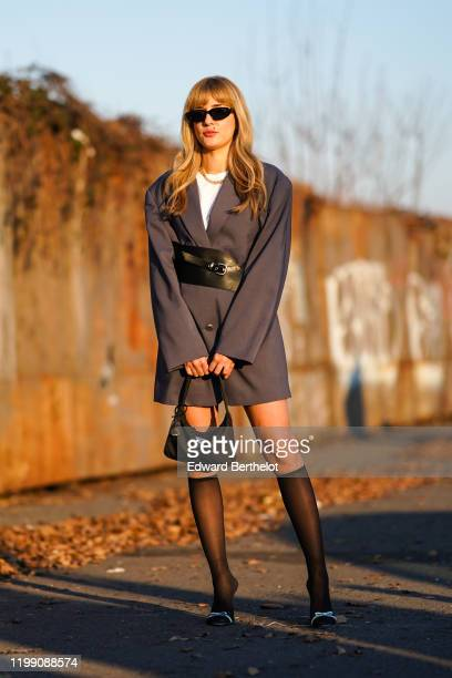 Eleonora Carisi wears sunglasses a white top a gray oversized blazer jacket dress a black leather corset a Prada bag tights shoes a necklace outside...