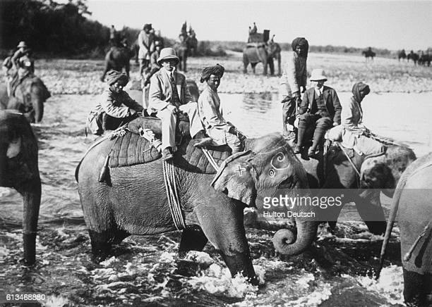 Elephants carry King George V the Indian Emperor and members of the Indian court across a river during a tiger hunt on the Emperor's Indian Durbar...