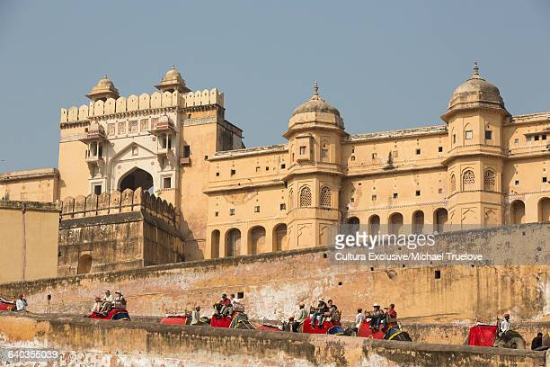 Elephants carrying tourists on ramparts at Amer Fort, Jaipur, Rajasthan, India