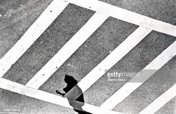 Elevated abstract view of a pedestrian's shadow on a crosswalk at the intersection of Mulberry and Grand streetsintersection of Mulberry and Grand...