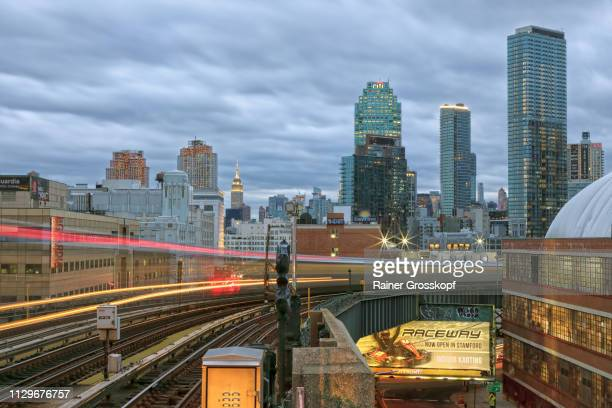 Elevated and moving Subway 7 with Queens Skyline in background