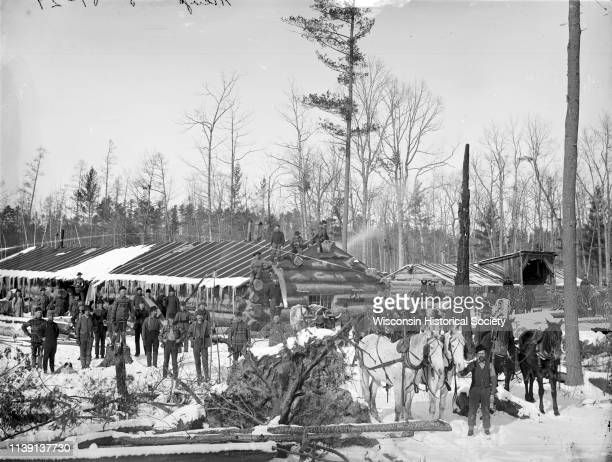 Elevated group portrait of loggers at a logging camp posing in the snow Black River Falls Wisconsin 1890 Some of the men are posing on the roof of...