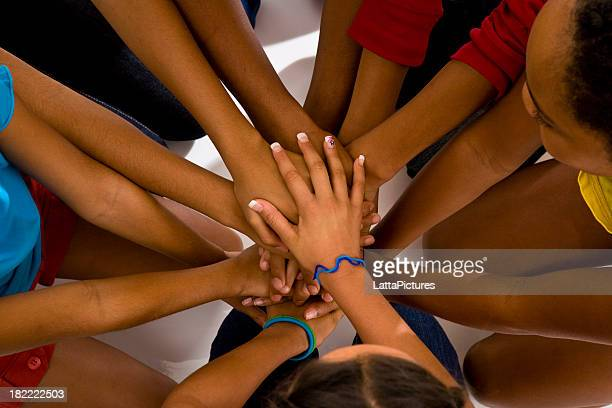 Elevated image group of stacked teenagers' hands