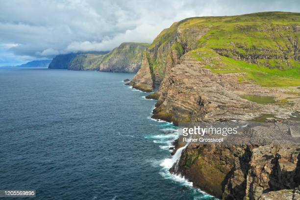 elevated panoramic view at rocky cliffs and a waterfall into the atlantic ocean - rainer grosskopf stock-fotos und bilder