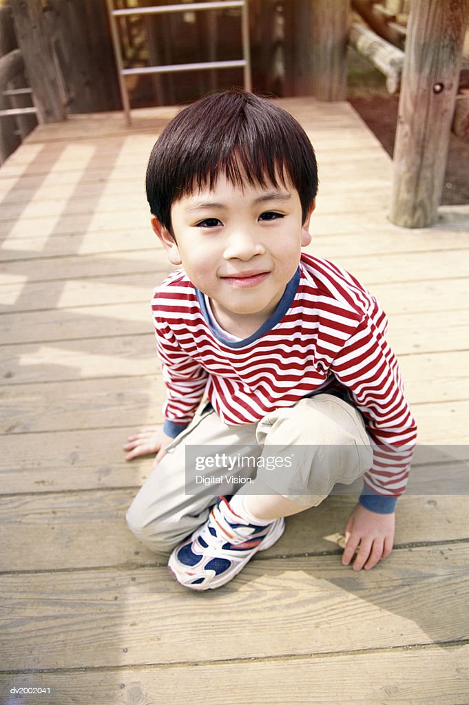 Elevated Portrait of a Young Boy Sitting on Decking : Stock Photo