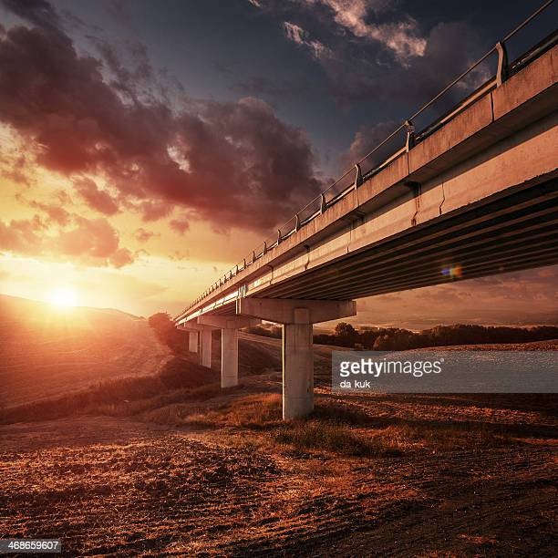 Elevated roadway at sunset against moody sky