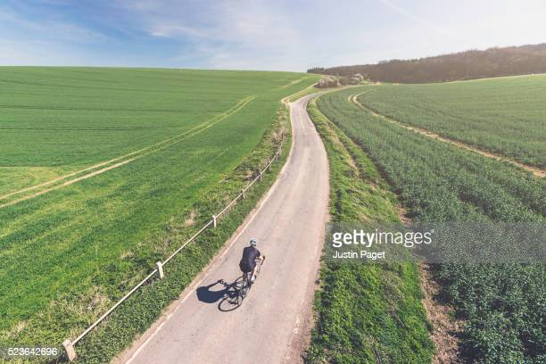 elevated shot of solo cyclist - shirt stock pictures, royalty-free photos & images