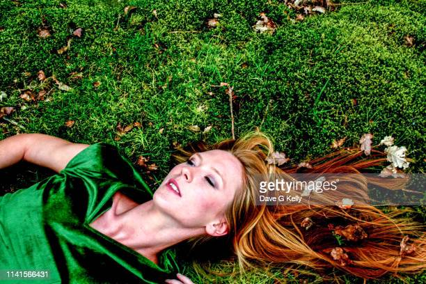 elevated shot of young woman on moss - green dress stock pictures, royalty-free photos & images